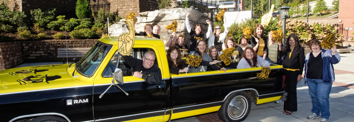 Campus Dining staff in pickup truck painted in Appalachian black and gold