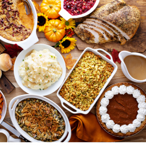A holiday meal spread with mashed potatoes, turkey, dressing, etc.
