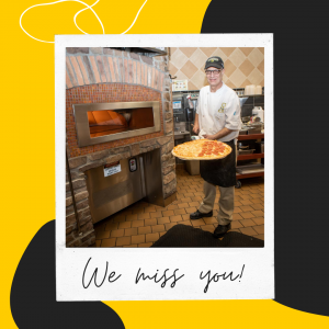 """Photo of Campus Dining team member pulling a pizza out of the oven with caption """"We miss you!"""""""